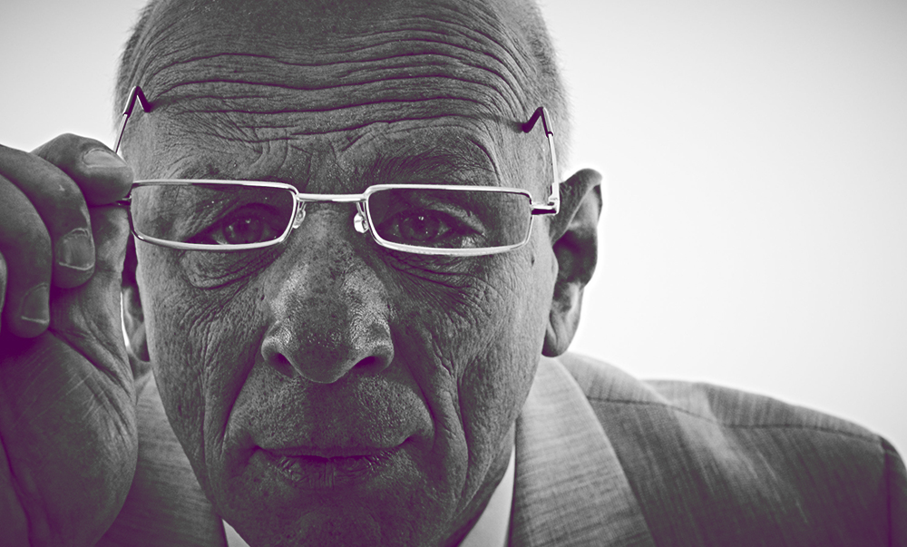 Elderly man lifting glasses up to face.